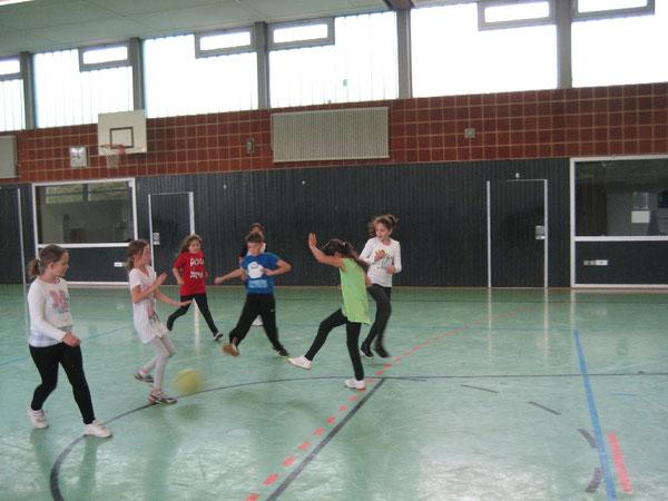 Mädchen und Jungen kickten den Ball durch die Halle