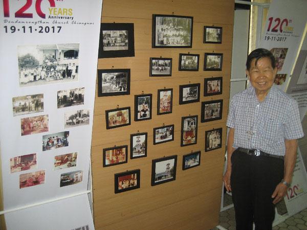 Professor Dr. Saad vor der Fotowand der Kirche