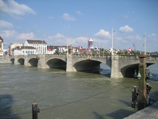 Stolz wehen die Nationalflaggen der Schweiz gemeinsam mit dem Stadtwappen der Stadt Basel über dem Rhein