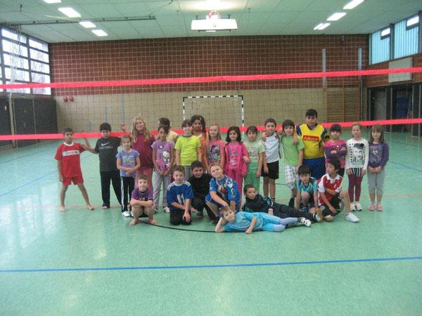 Die Nachwuchsvolleyballerinnen und Nachwuchsvolleyballer lächeln in die Kamera