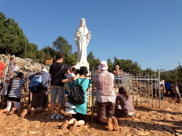 don Gigi assorto in preghiera, con alcuni parrocchiani