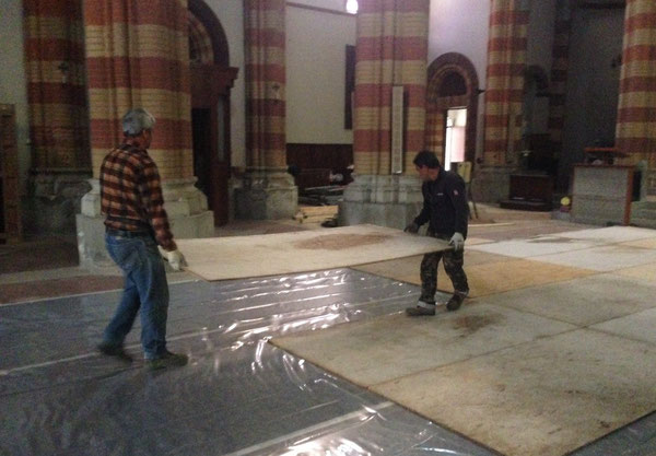 Giuseppe e Vincenzo coprono il pavimento a protezione.