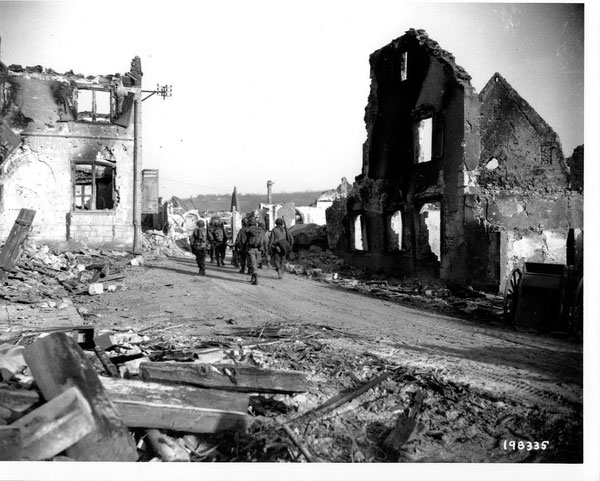 Men of L Company, 15th Infantry march through Bennwihr, December 27, 1944 (Photo courtesy National Archives)