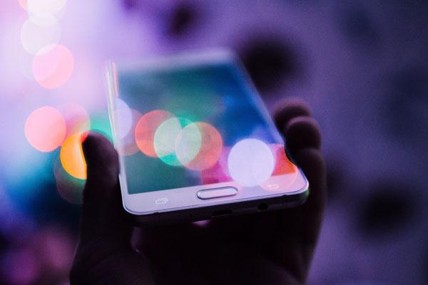 Eine Hand hält ein weißes Smartphone mit dem Display nach oben.