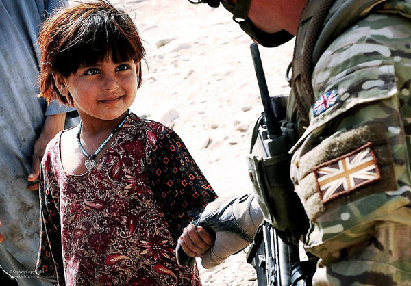 A young girl in a village in Helmand Province, Afghanistan holds the hand of a soldier of 3 Mercian Regiment, A Company, on the opening day of her new school.
