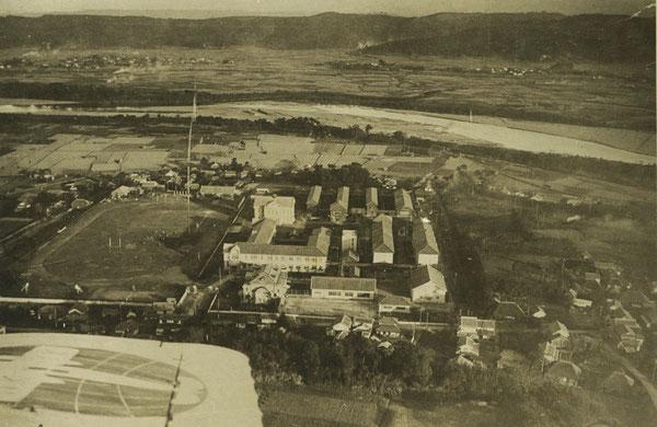 大分高商の航空写真(画面左が北の方向)。写真中央に校舎群と、その北側にグランドが見える。この写真の左下に正門が見えている。写真上(西側)に大分川が広がっている。(著者所収)