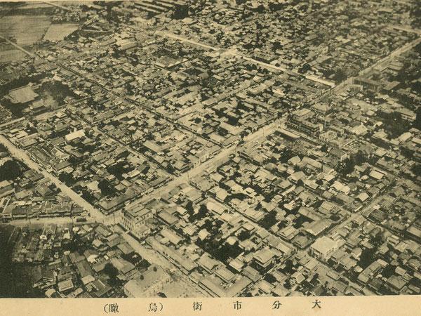 ホーンビー先生が10年に亘る大分高商勤務の最後の年となった昭和8年(1933年)頃の大分市街(航空写真)。写真の左(南)が大分駅の方向で、右(北)が府内城がある方向。写真の中央を斜めに走る広い通りが現在の中央通り(当時の電車通り)で、大分合同銀行や竹町通り入口から続く白い天幕が見える。電車通り沿いの大分合同銀行(戦後の大分銀行)の北側道路を挟んだ広い空地に、トキハ百貨店が昭和11年に建設される。大分市勢要覧(昭和8年):著者所収