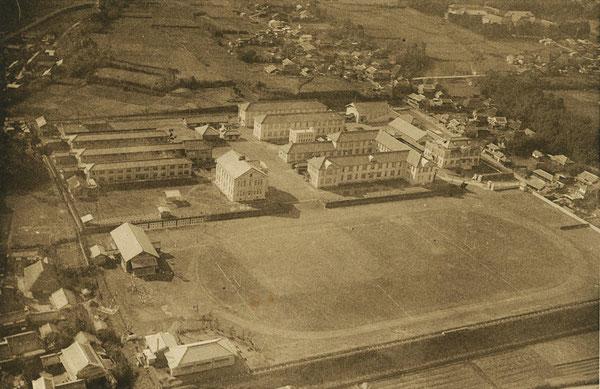 大分高商の航空写真(画面下が北の方向)。写真中央に校舎群と、その北側にグランドが見える。また、写真右上端には大分中学(現在の大分上野丘高校)の校舎が見える。(著者所収)