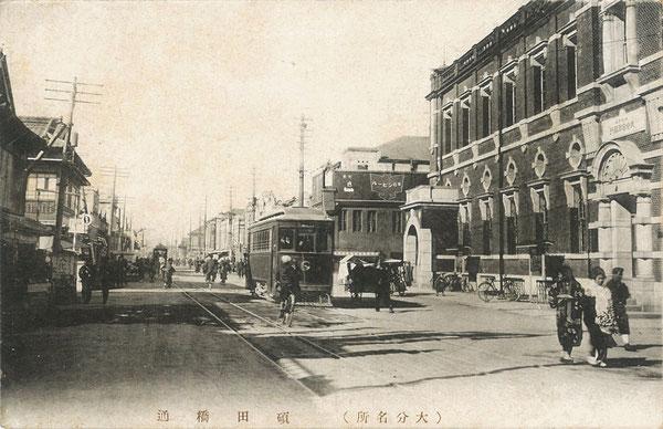 昭和初期の碩田橋(おおいたばし)通りの絵葉書写真。右手に大分合同銀行(昭和2年(1927年)に竹町2丁目の旧大分銀行と二十三銀行が合併)が見え、二車線の別大電車が行き交っている。(著者所収)