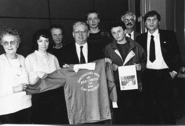 Bei einem Besuch 1993 überreicht eine Wolfsburger Delegation dem Aussiedlerbeauftragten Dr. Horst Waffenschmidt eine Dokumentation über sozialsportliche Aktivitäten ein Sportrikot