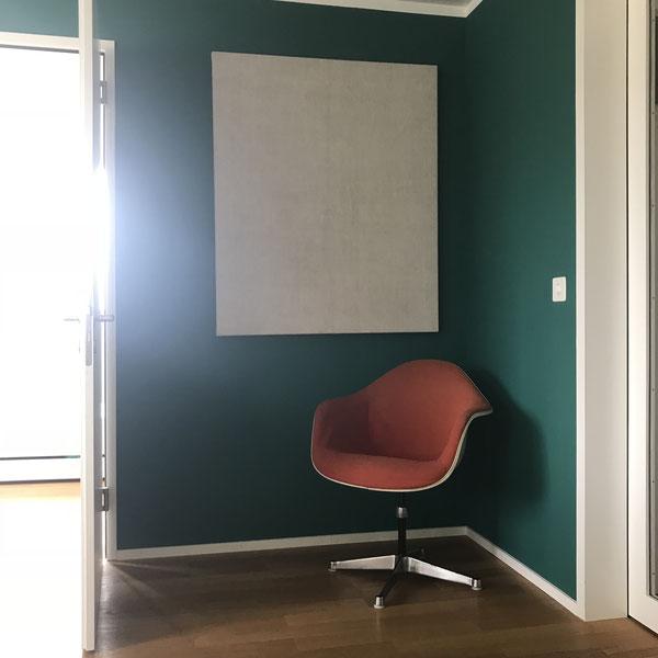 Oranger Vintage Eames Drehsessel vor grüner Wand in Kombination mit Stoffbild aus antiker Leine.