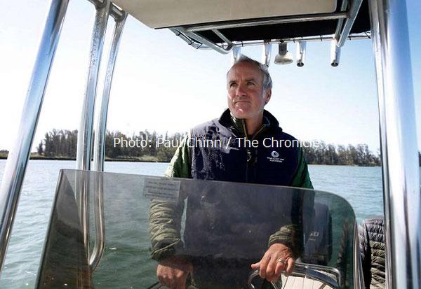 モントレーベイ水族館ラッコプログラムの動物ケアコーディネーター、カール・メイヤーが、ラッコの回復を行っているモスランディングのエルクホーン湿地帯をボートで進む。