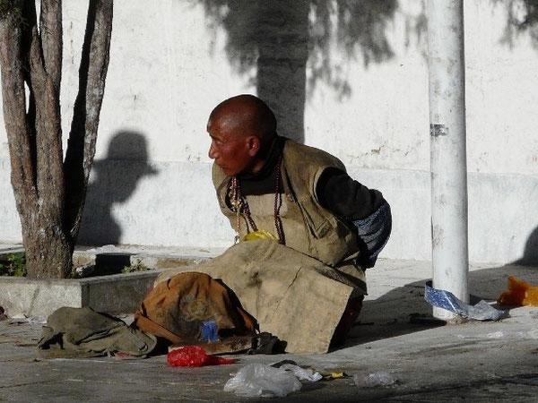 """Un pelerin """"rampant"""" vetu de son tablier de cuir pour se proteger quand il s'allonge sur le sol. Sur son front, une cale s'est formee."""