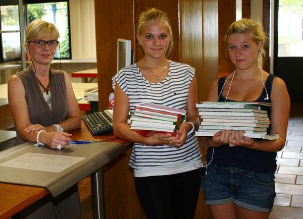 Frau Ochsenreither (verantwortlich für die Organisation der Schulbuchausleihe bei der Stadt Wörth) und Julia Emeljanow (10d) und Melissa Benz (10d), die gerade ihre nachbestellten Bücher in Empfang genommen haben