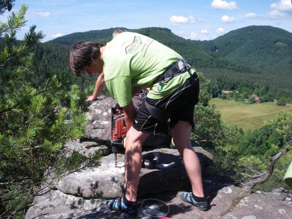 Nico Zimmermann bohrt das Loch für die Gipfelbuchhülse auf dem Rheinturm.