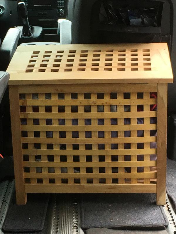Eine Holzbox prall gefüllt mit Stoffhäuschen und Kissen