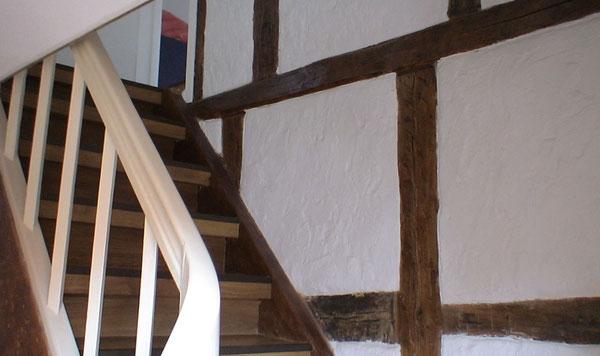 Das Treppenhaus zum Dachgeschoss mit freigelegtem Fachwerk; die Treppe ist etwas steil