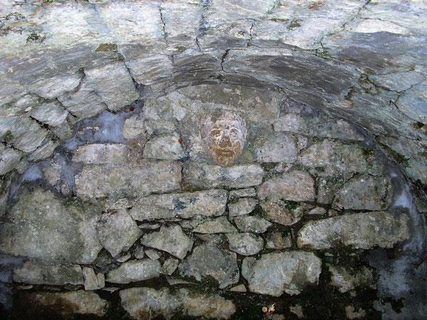 Sous la voute de la Fontaine des Cagots, un masque de pierre marque le rappel des vieux rites qui avaient cours dans le quartier...