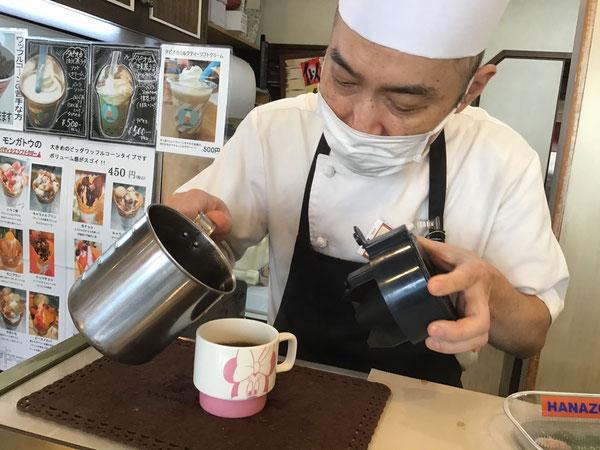 ステンレスピッチャーでコーヒーを注ぐシェフ モンガトウ