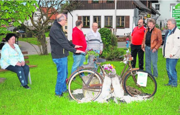 Das Schmuck-Fahrrad soll im Laufe des Jahres einem Brunnen weichen, den sich die Dorfgemeinschaft vom Erlös des Heimatfestjahres leisten will. Festleiter Ewald Zetzl (Zweiter von links) stellte das Projekt vor. Bild: fjo