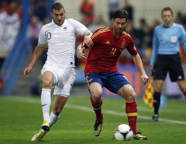 Xabi Alonso pelea por un balón con su compañero en el Real Madrid Karim Benzema.