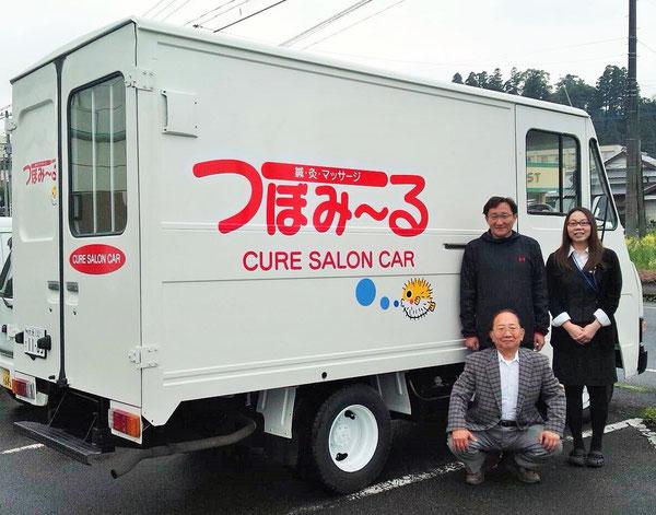 児玉 前事務長さん(後列左)と鍼灸マッサージ専用の移動車両です。