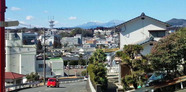 当院前の道路の坂を上った三重中学付近からみた風景です。左の国旗がある建物が豊後大野警察署で、遠くに冠雪している久住山が見えます。