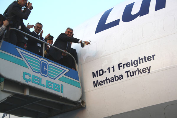 Orhan Birdal of Turkey's State Airports Authority is sprinkling blessed water on the name of the plane  /  pictures: hs