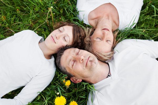 meditierende Familie liegt im Gras, auf dem Rücken liegen, träumen, Frieden in der Familie, entspannte Menschen, Vertrauen, Liebe, Frühling, Egofrei Sein