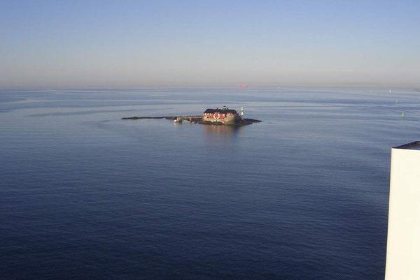 Ein einsames Haus mit Leuchtturm im Meer