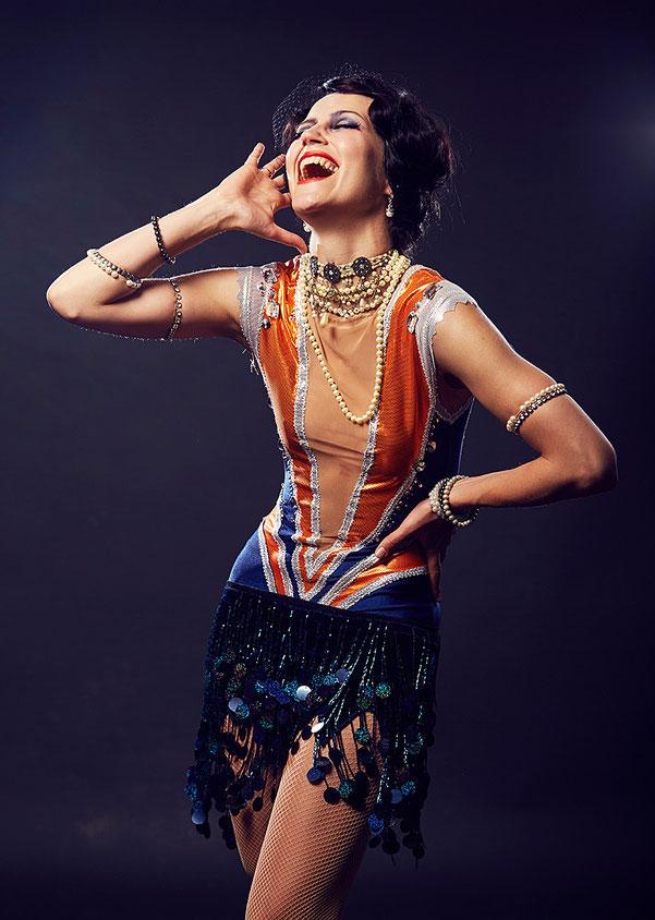 Tänzerin posiert lachend in 20er Jahre Kostüm