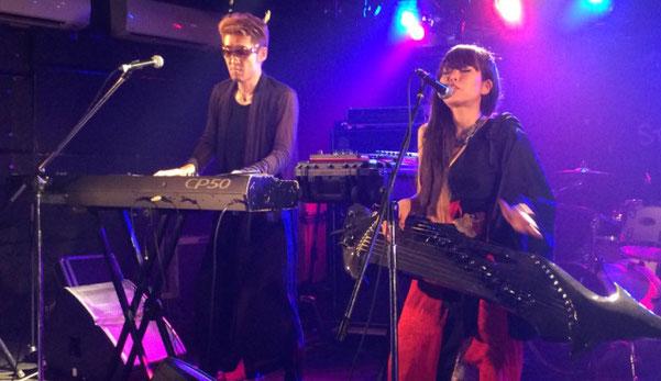 月宵の「柿木原 こう」がエレ琴、「フジキ テツ」がピアノをステージで演奏している場面