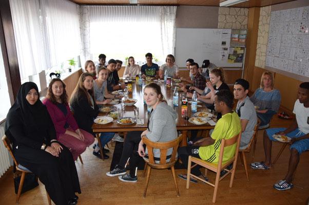 Schüler des BvS und junge Geflüchtete mit Mitgliedern des Flüchtlingshilfevereins beim gemeinsamen Essen