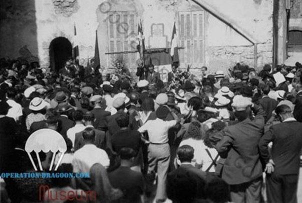 Unique photo connue de l'inauguration de la plaque Justin BLANC à Montauroux en 1945, face à la plaque, Abel TALLENT récite un éloge funèbre à son chef et camarade mort en déportation au camp de Dachau.