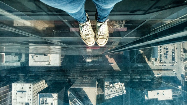 looking straight down from the willis tower skydeck standing in one of the ledges looking at chicago streets and cars and buildings