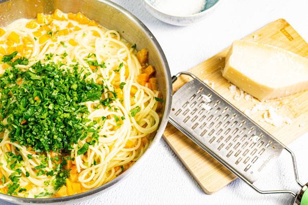 Die Pasta wird mit der Sauce, Gemüse und den frischen Kräutern im Topf vermischt und dann auf einem Teller angerichtet