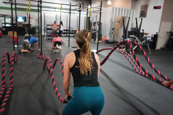 In einem Fitnessstudio trainieren Sportler im Funtional Bereich. Die Frau im Vordergrund trainiert mit den Battle Ropes die Kraftausdauer.