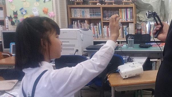 小さいカメラの向こうの先生に向かって、世界に一つのオリジナル乾電池を披露します