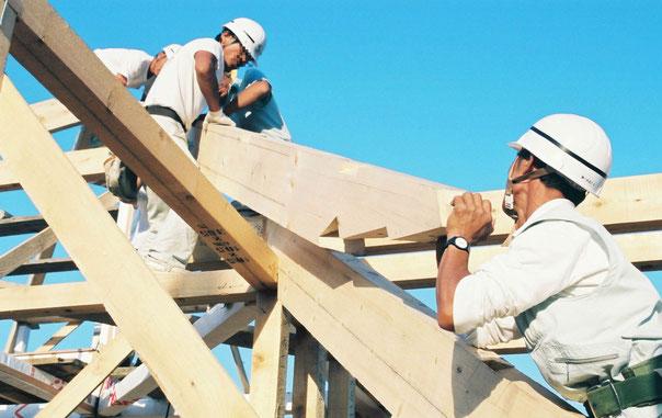 北海道の青空の下、ヘルメットをかぶった地元の大工さんたちが木造の家を建てています。家は、まだ骨組みだけの中、一人の大工さんが重そうな柱を下から屋根に上げようとしていて、それを上から三人の大工さんが引っ張り上げようとしています。