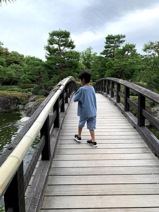 素敵な木製の橋の上で何やら楽しむガーデンドクターJr.