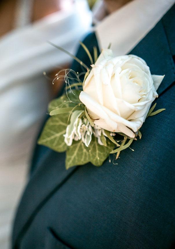 Eine helle Blume am Jackett des Bräutigams