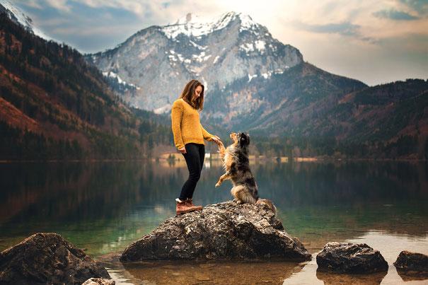 Fotografin Jasmin Hummer mit ihrer Hündin Nala auf einer Bank im Herbstwald
