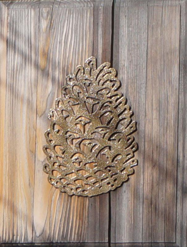 Détail de la pomme de pin sculptée sur le portail