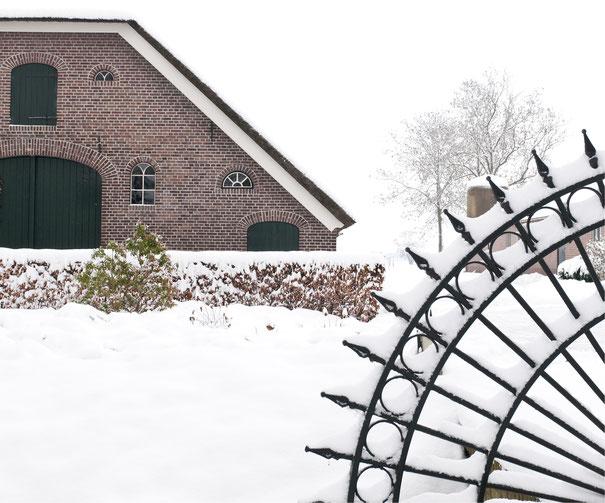 Boerderij met hek in de sneeuw