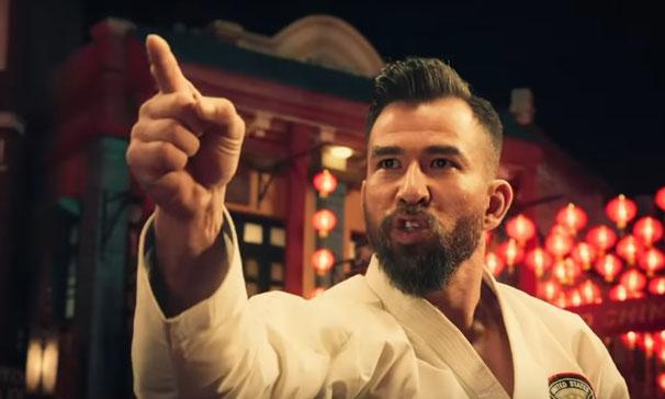 Auf dem Bild ist Chris Collins zu sehen, der einen weißen Karateanzug trägt und mit dem Zeigefinger in eine Richtung zeigt.