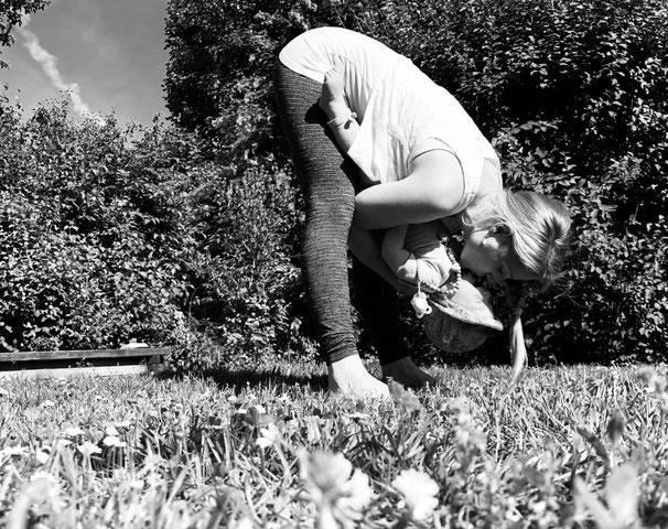 Das Yogamami mit dem Yogababy am Kuscheln in einer Vorwörtsbeuge