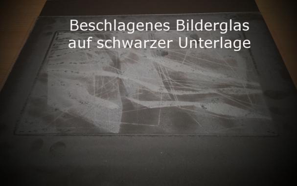Bildergals ersetzen - Bilderglas reinigen: Beschlagenes Bilderglas auf schwarzem Hintergrund