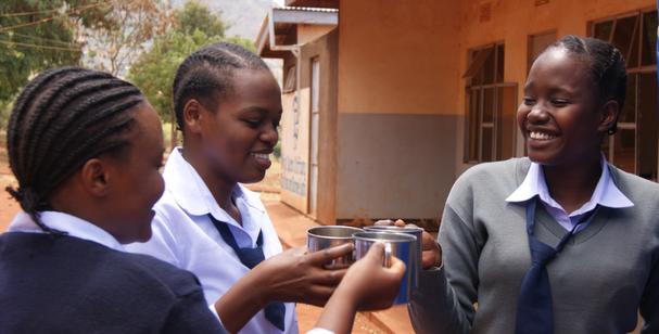 Drei tansanische Schülerinnen prosten sich mit ihren Wasserbechern zu und lachen