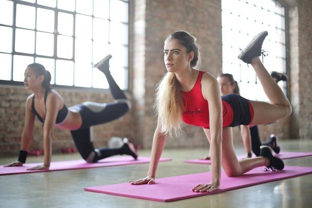 In einem Sportraum sind drei Frauen und trainieren Fitness. Sie stützen sich auf Yogamatten ab und heben das linke Bein in die Luft, um das Gesäß zu trainieren.