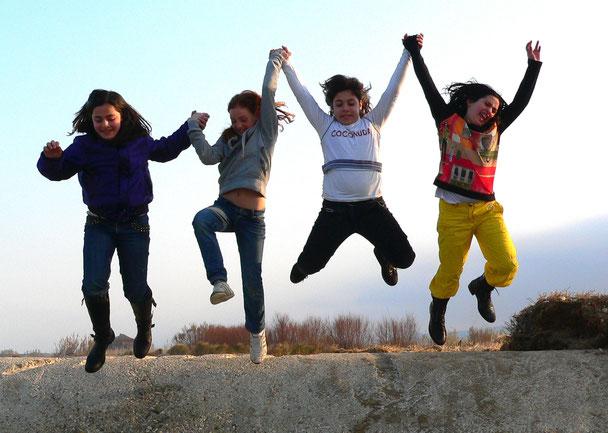 Das Bild zeigt vier Kinder, die sich an den Händen halten und gemeinsam in die Höhe springen.